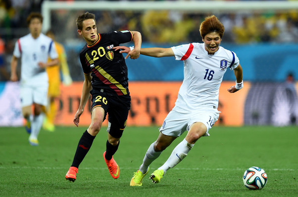 Adnan Januzaj of Belgium and Ki Sung-yueng of South Korea compete for the ball during the 2014 FIFA World Cup Brazil Group H match between South Korea and Belgium at Arena de Sao Paulo on June 26